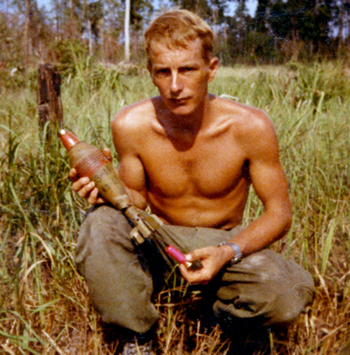 The author with a case of enemy Chi Com 82mm mortar rounds I found in the jungle. We must have scared them off and they left them behind.