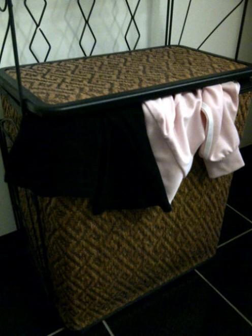 The overflowing laundry bin~