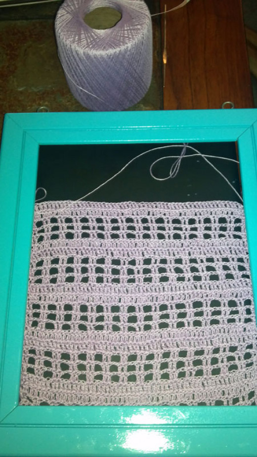 Material insert for frame: an open weave crochet mesh pattern.