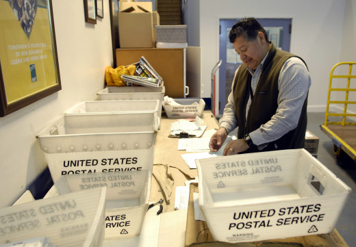 A postal worker sorting mail at the post office. Can you imagine how much mail they see every day?