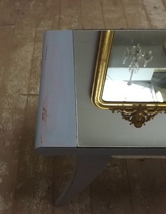 A vintage table with mirror inset. Great for reflecting light and creating visual interest!