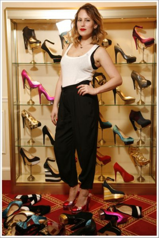 Charlotte Dellal surrounded by a selection of her shoe styles.