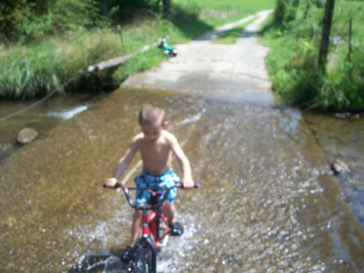 My grandson Colton riding his bike through the creek on a hot summer day