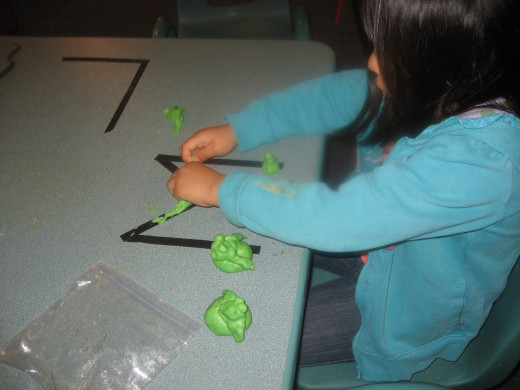 Tape letters help a child make playdough letters.