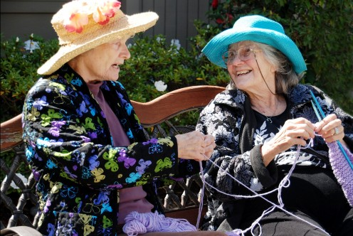 Two elderly women at a Silverado Senior Living Center engage in conversation and activities.