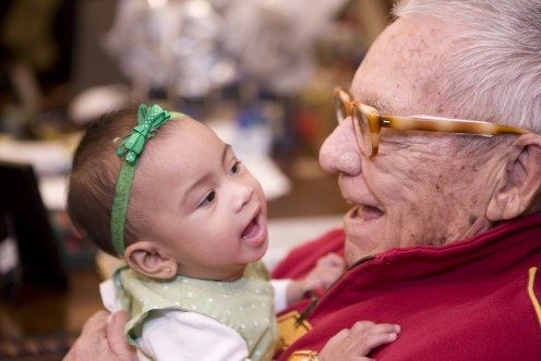 An elderly male resident at a Silverado Living Care Center holds a child.