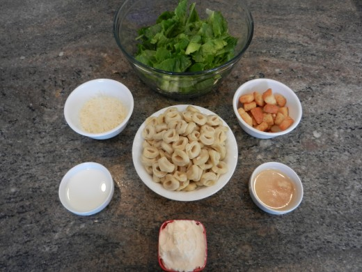 Ingredients for tortellini salad. Garlic and lemon juice are in the same bowl.