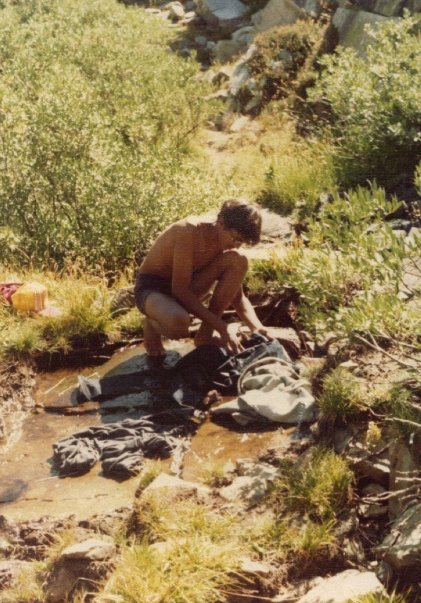 Danny washes his clothes in the creek.