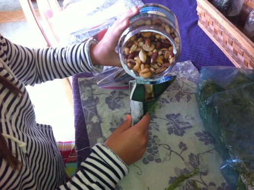 Filling the paper cone with mixed, roasted, salted nuts.