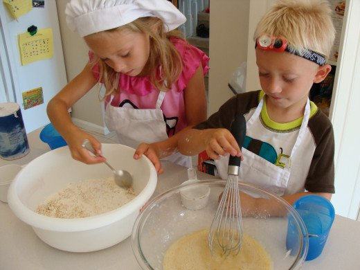 Grace mixes the dry ingredients while Alex handles the wet.