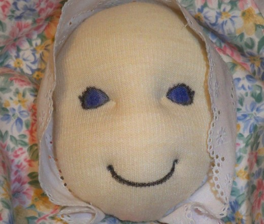Begin forming facial features by hand sewing with heavy thread on a large needle.  Attach bonnet and/or hair at this point.