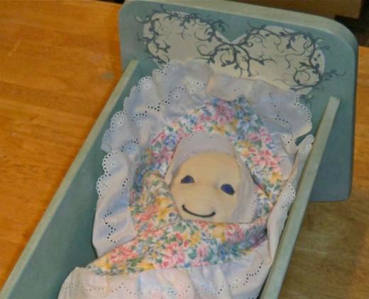 Tucked into her handmade cradle.