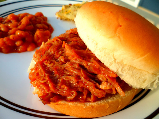 Use tongs to add pulled pork to sandwich buns.