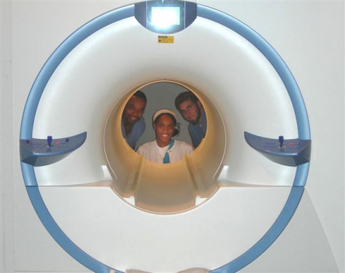 Radiographers and nurses looking into an MRI machine