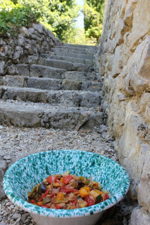 Serving dish of ratatouille on the steps of an old stone sheperd's cabin in Provence