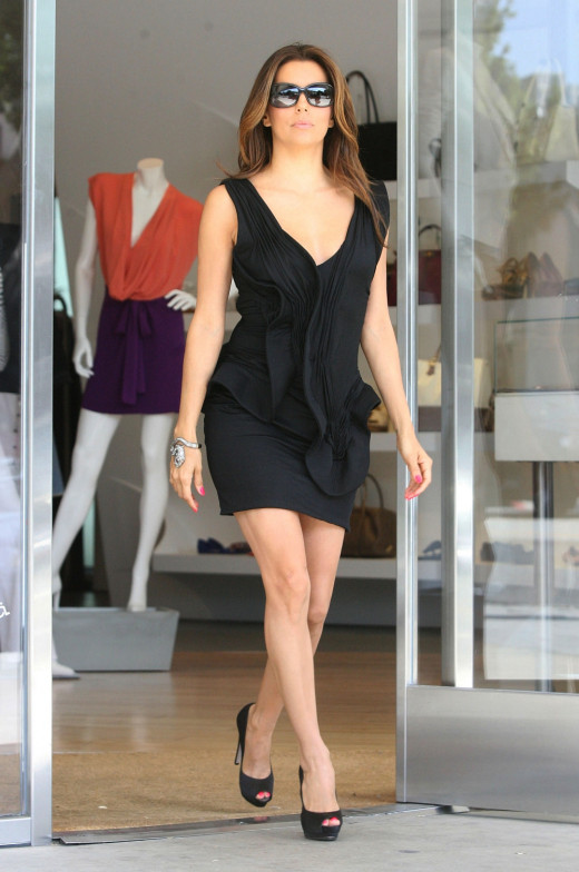 Stepping out in a low cut and short little black dress with satin pumps