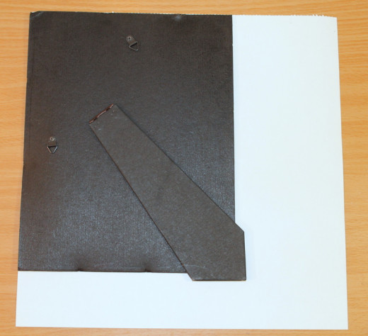 Place frame back, or other sheet of cardboard, on your decorative paper, lining two of the edges up, as shown.