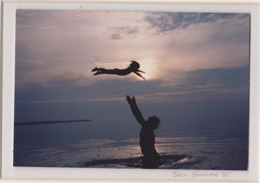 Kallie being thrown in the air by her dad over Lake Michigan with the sun silhouetting them.