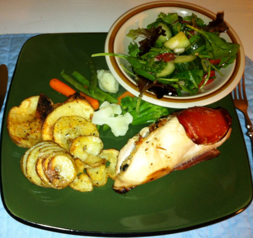 Stuffed chicken breasts with oven fries, mixed vegetables, and a side garden salad.