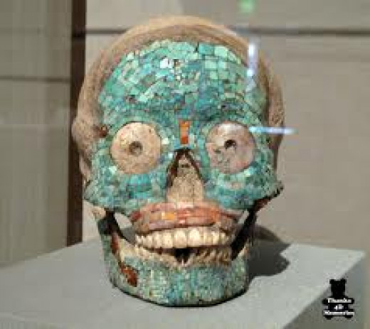 Turquoise encrusted skull image of the diety.