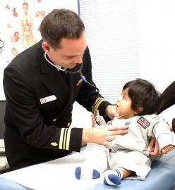 U.S. Naval Hospital Yokouska, Japan (October 27, 2003) -- Family Nurse Practitioner Lieutenant Commander Michael Service cares for a young girl at the hospital.
