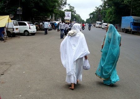 A Jain Nun and Lay Woman walking on the road.