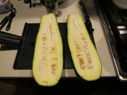 """Cut a large zucchini in half, but not exactly down the middle.  One side needs to be larger than the other to make a deep zucchini """"bowl""""."""