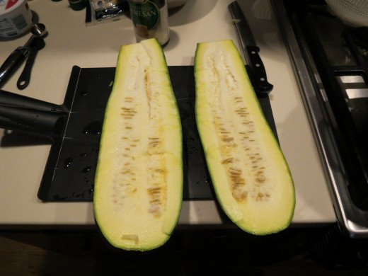 "Cut a large zucchini in half, but not exactly down the middle.  One side needs to be larger than the other to make a deep zucchini ""bowl""."
