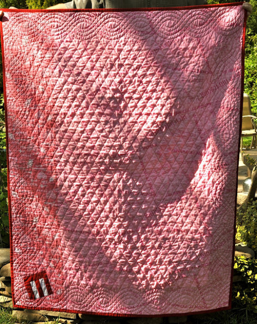 Barb has pieced two different pieces of pink fabric for the back of this quilt. Most of the backing is one piece, but there is a small strip on the left that is another, but similar, fabric.