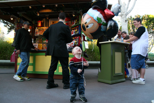 The author's 2 year old son enjoys a balloon at Christmastime in Downtown Disney.