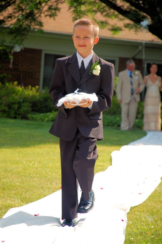 A ring bearer walking down the aisle