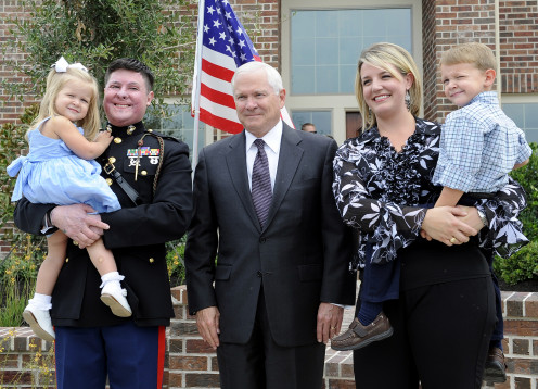Retired Capt. Dan Moran, U.S. Marine Corps, wife Teal and their two children, with Secretary of Defense Robert M. Gates outside his new home built by Perry Homes and non-profit organization Helping a Hero in Cypress, Texas, Aug. 31, 2009.
