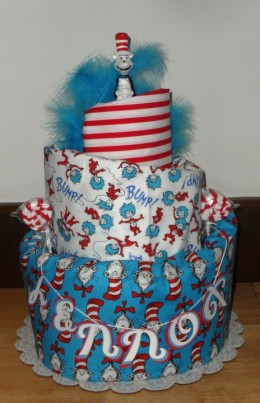 "This topsy turvy cake was inspired by Dr. Seuss' ""The cat in the hat. Included a handmade Receiving Blanket and Burp Cloth with a keepsake statue of the ""Cat"" himself."