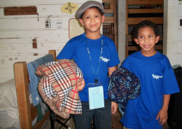 Campers settling into their cabin with blankets donated by Project Linus.