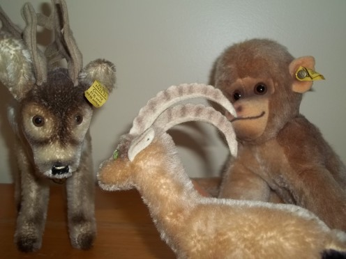 These are all Steiff animals.  The reindeer has all of his tags, the monkey has the ear tag, but is missing the chest tag and the mountain goat is missing all of the tags. Look closely and you'll see the hole in his ear where the button used to be.
