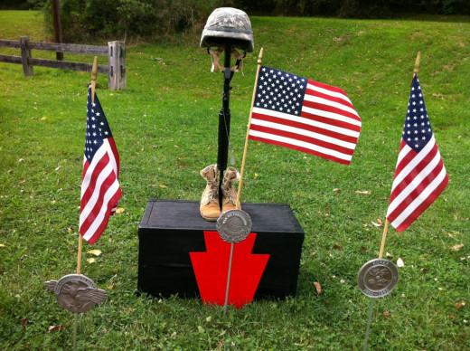 """Fallen Soldier Battle Cross"" (Boots, Rifle, Helmet) set up in memory of Sgt. Jan Argonish."