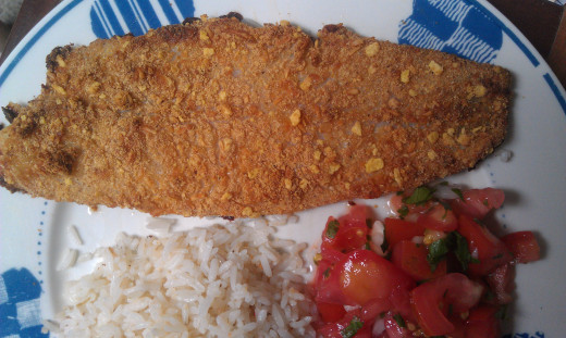 Parmesan crusted fish served with rice and chimichurri, a lime-marinated tomato and onion salad I discuss in another Hub referenced below.