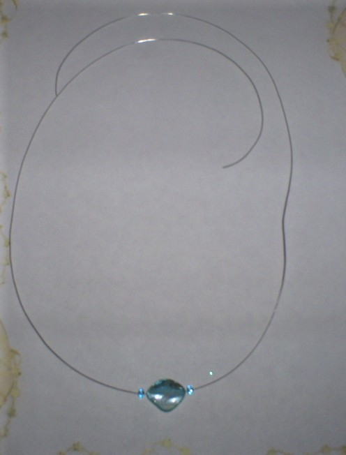 Add a blue seed bead to each side of the necklace.