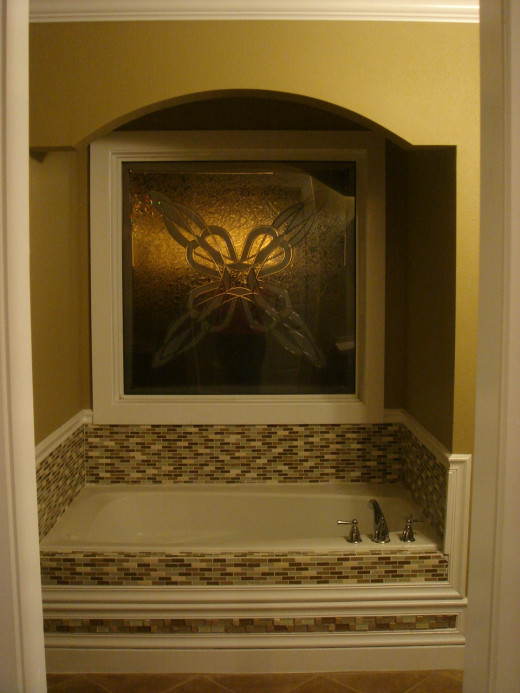 The decorative picture window and custom tiled tub surround make this area the focal point of the bathroom.