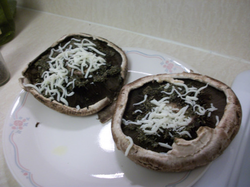 Put the paste on each mushroom, then sprinkle some mozzarella cheese on each one.
