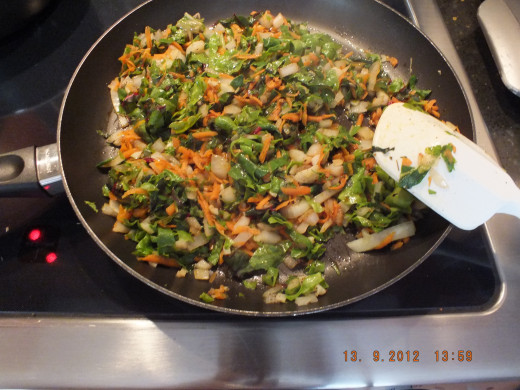In goes the swiss chard and garlic. They don't need as much time on the heat.
