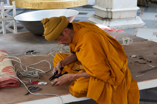 A Buddhist monk doing electrical work … mindfully.