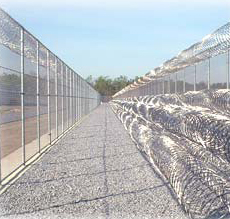 Concertina razor wire surrounds prison.