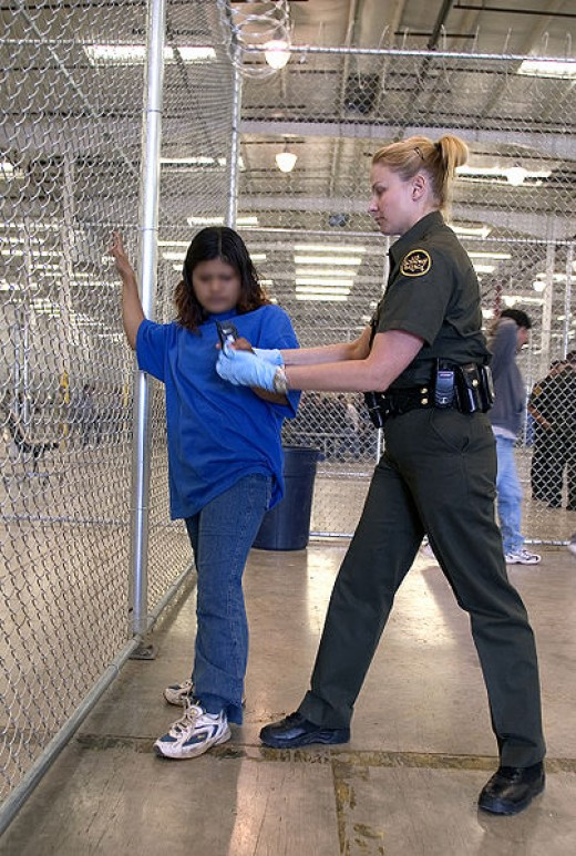 CBP Border Patrol agent conducts a pat down of a female Mexican being placed in a holding facility.