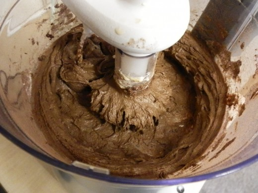 Add flour, whole egg, egg yolk, vanilla and cocoa powder to creamed sugar-butter mixture and blend