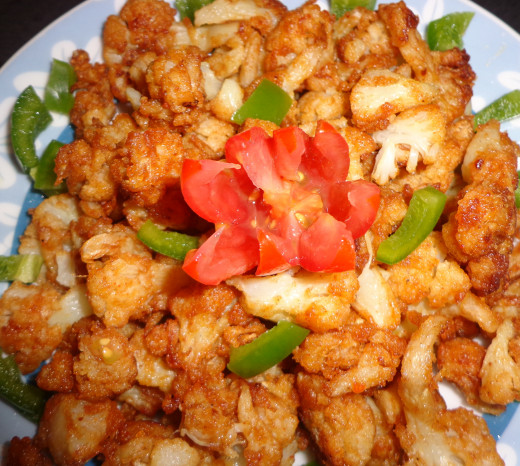 Fried Cauliflower or Gobi chilli garnished with Tomato & Capsicum