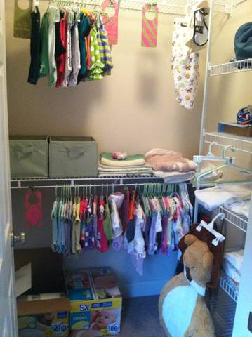 Green Organizational Bins, Lion playmat (it's hanging to dry, machine washable), 50 fuzzy blankets I've never used (and one that I have), receiving blankets, swaddler that I've never used (hanging above the blankets), clothes in every size.