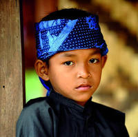 Iket kepala wrapped around the head of young Insonesian kid