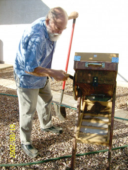 Cranking the bellows and shaking the riffle box.