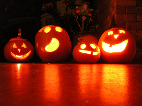 Jack O' Lanterns sit cheerfully on a porch.
